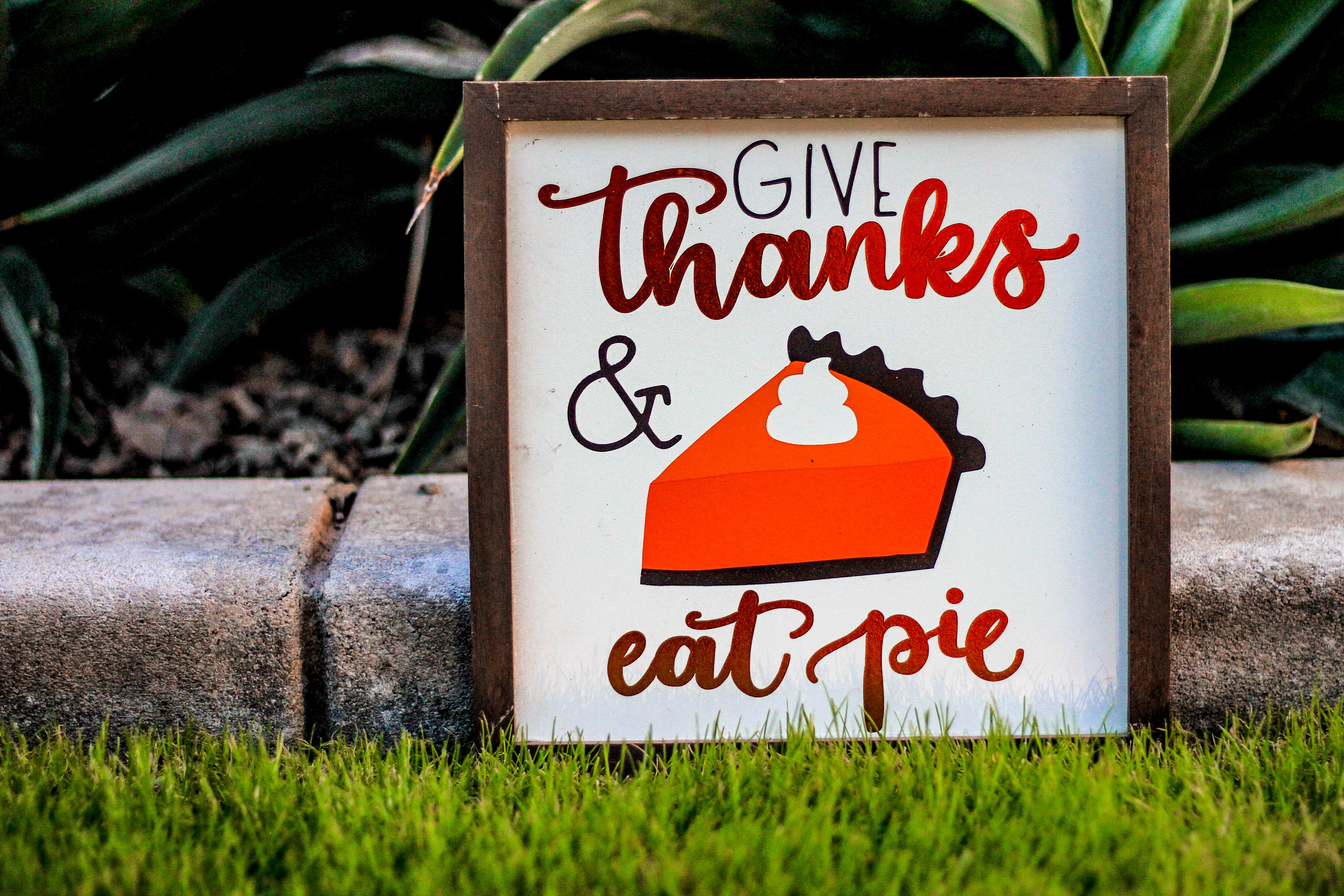 small sign in a yard that says give thanks and eat pie