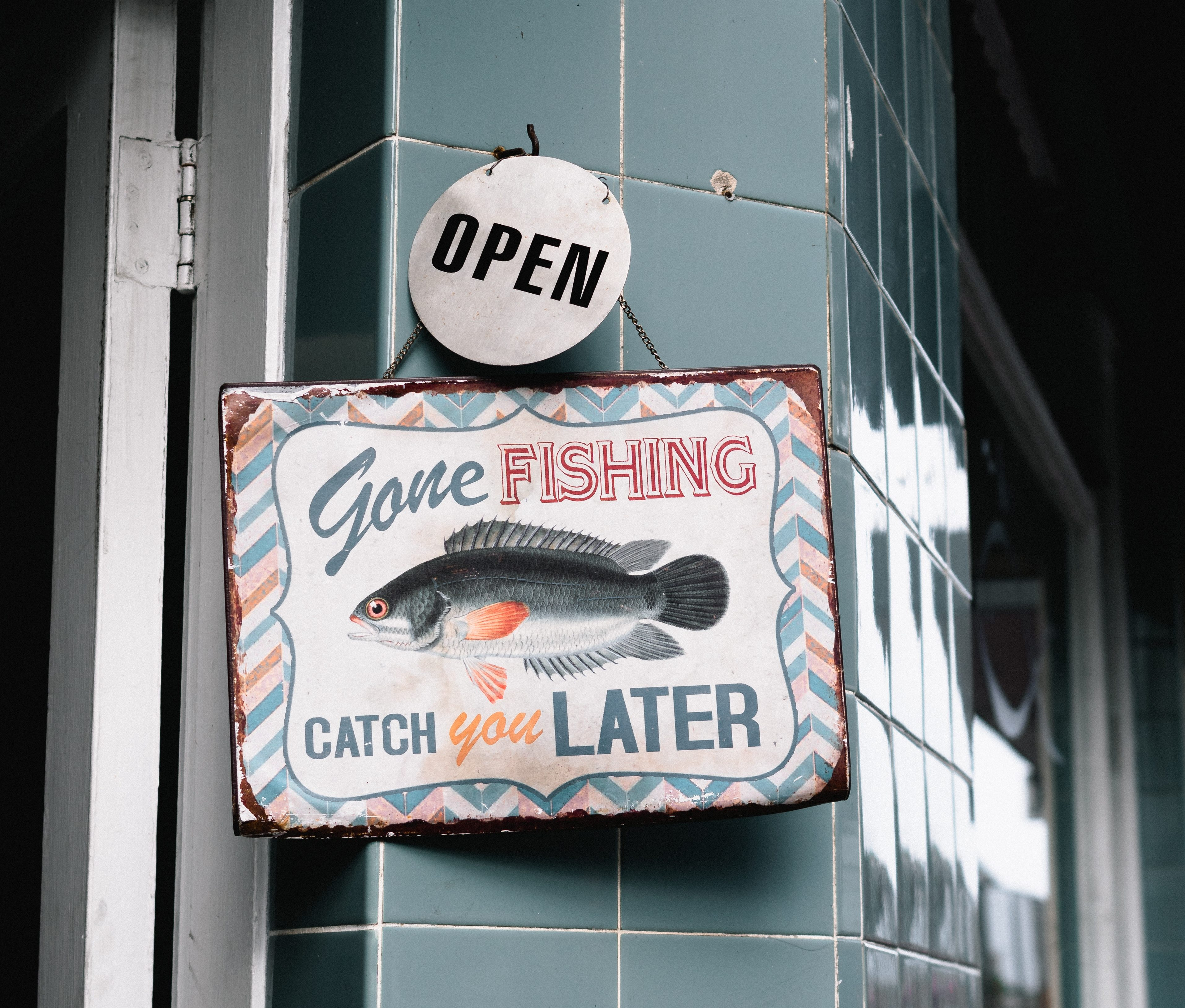 "A sign hanging with a fish on it by the front door of a shop that says ""gone fishing, catch you later""."