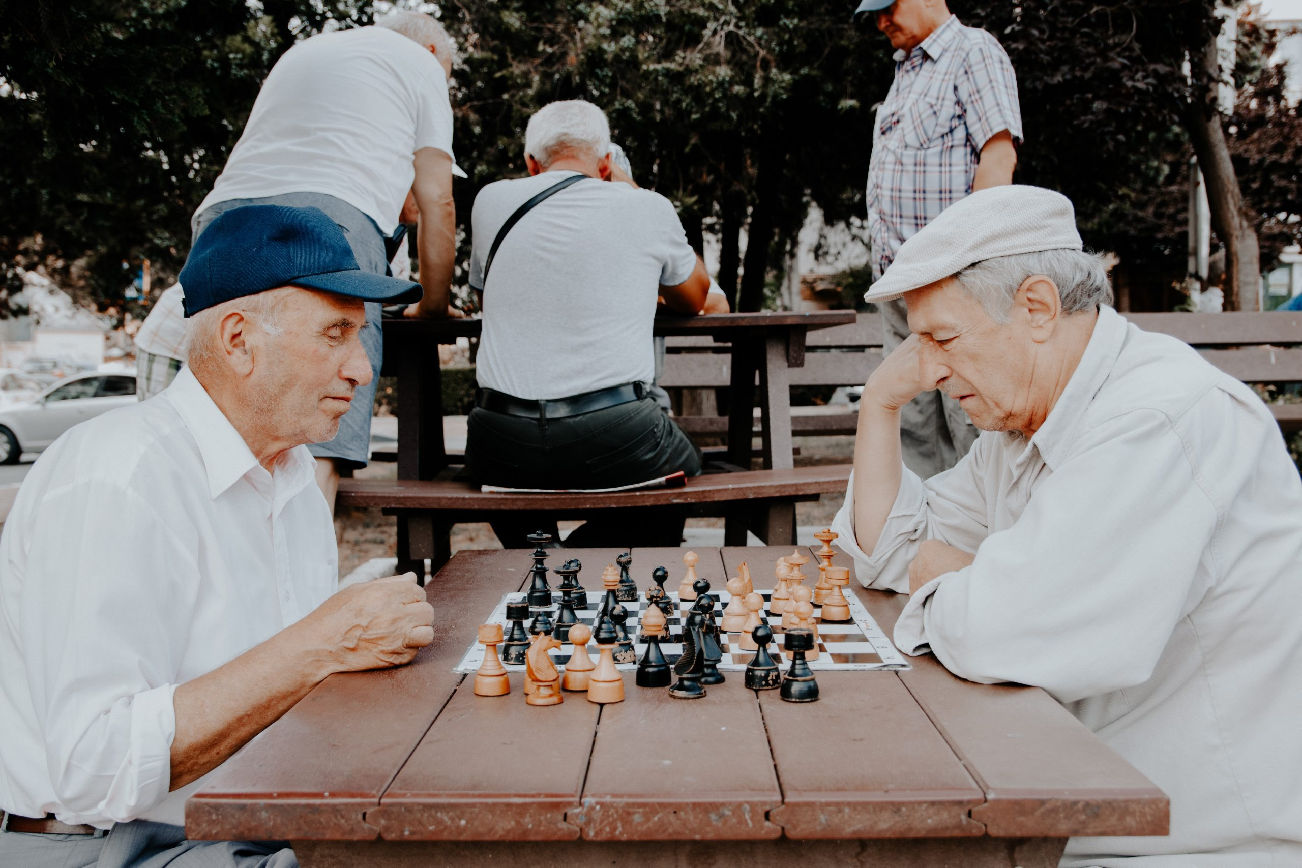 At a picnic table at a park, two older men in white dress shirts play a game of chess. Five senior citizens can be seen convening at another picnic table in the background.
